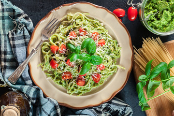 Vegetarian pasta spaghetti with basil pesto and cherry tomatoes