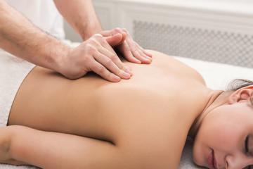 Closeup of hands massaging female shoulders and back