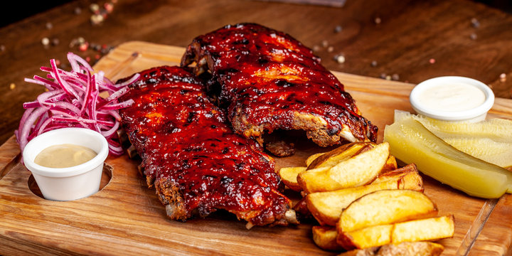 Fried ribs air fryer in marinade, with tartar sauce on a wooden board. With French fries in a rustic way and vegetables. concept of a beautiful serve in a restaurant or in a cafe.