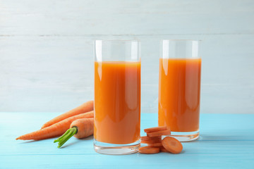 Glasses with carrot juice and fresh vegetable on wooden table