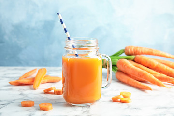 Mason jar with carrot juice and fresh vegetable on table