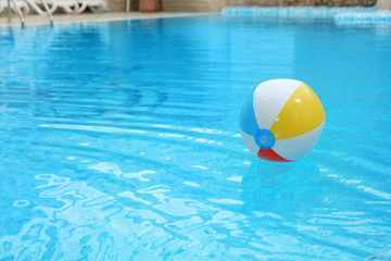 Colorful inflatable ball floating on water in swimming pool