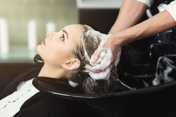 Beautician washing woman's head in beauty salon