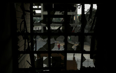 A Palestinian man looks at the Ministry of Religious Affairs that was damaged by Israeli air strikes in Gaza City