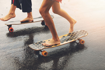 friends riding longboards on wet city street at sunset