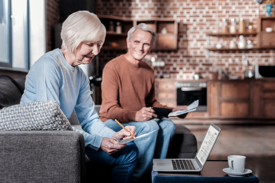 Bill calculation. Cheerful blonde keeping smile on her face while working at home