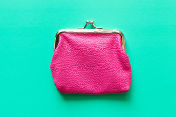 Pink wallet on turquoise background . Close up. Top view