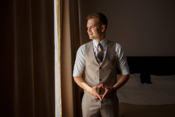 Cheerful attractive man in stylish suit is ready for successful business day, looking at the window while standing in the bedroom. Indoors.
