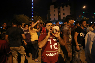 Iraqi protesters shout slogans during a demonstration in Kerbala
