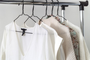 Minimalist capsule wardrobe showcase. White and beige tone silky shirt and knitwear hanging on a clothes rack. Selective focus, horizontal