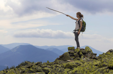Young slim blond tourist girl with backpack points with stick at foggy mountain range panorama standing on rocky top on bright blue morning sky background. Tourism, traveling and climbing concept.