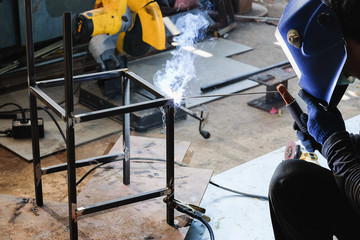 Industrial worker welding metal steel to make chair. Flash burn, ultraviolet light, sparks, infrared light effect, technician use welding mask to protect the eyes.