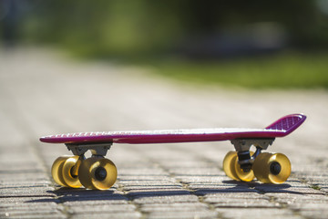 Close-up of child plastic pink skateboard isolated on pavement against bright white and green blurred bokeh background. Sport, recreation, fun and plays concept.