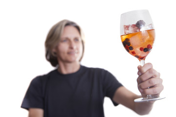 Woman holding a glass with juice, ice and berries.  Isolated on white background.