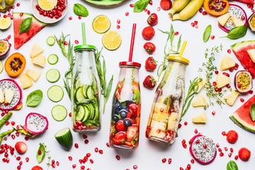 Summer clean and healthy lifestyle and fitness background with various infused water in bottles, colorful sliced ingredients: fruits, berries, vegetables, herbs on white  background, top view