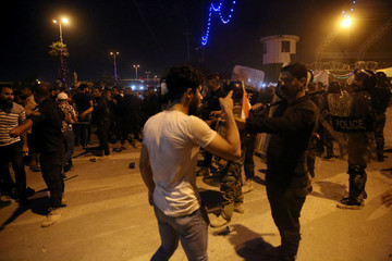 Iraqi protesters scuffle with security forces during a protest in Kerbala