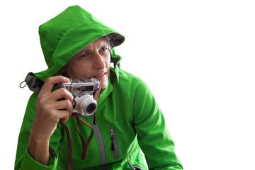 Woman with green jacket and hood holding a vintage camera.