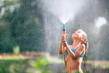 Cute little girl pours herself from the hose, makes a rain. Hot summer day pleasure