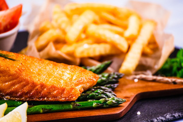 Fried salmon with french fries on wooden table