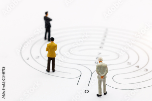 Miniature people: Businessman standing on start point of maze and