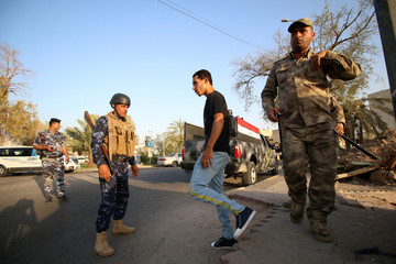 Iraqi security forces check the protesters near the main provincial government building Basra