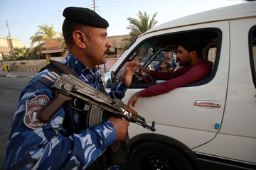 Iraqi security forces stand guard near the main provincial government building Basra