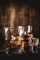 Two whiskey shot glasses on dark wooden background, with ice cubes, copy space