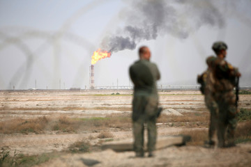 Iraqi security forces stand guard inside the west Qurna 2 oilfield, during a protest in north Basra