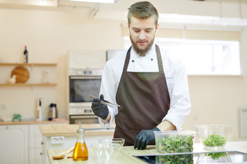 Waist up portrait of handsome bearded chef cooking in restaurant kitchen standing at wooden table, copy space