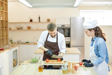 Portrait of professional cook working in restaurant kitchen with female su-chef, both cutting vegetables standing at wooden workstation, copy space