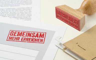 Roter Stempel auf Unterlagen - Gemeinsam mehr erreichen