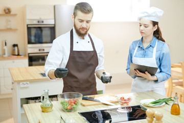 Portrait of two young professional chefs working in restaurant kitchen together cooking and seasoning salad standing at wooden table