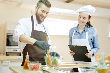 Waist up portrait of two professional chefs working in restaurant kitchen together cooking and mixing salad