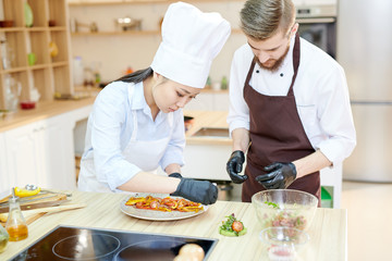Portrait of two professional chefs cooking delicious dishes in modern kitchen standing at wooden table , copy space