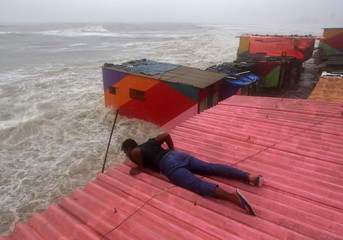 A man inspects his house during high tide at the sea front in Mumbai