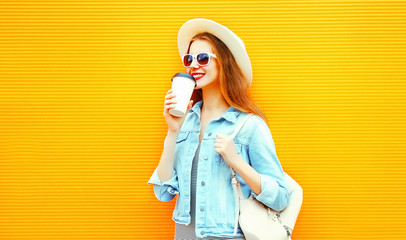 Cool girl drinks a coffee on a orange background