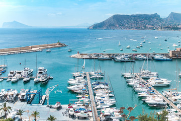 Top view of the marina, port with many boats, some moored, others sail on the sea. In the distance a picturesque mountain with many houses. The city of Calpe in Spain, Valencia, Europe.
