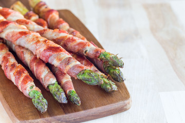 Green asparagus wrapped with bacon on wooden board, horizontal, copy space