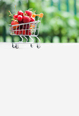 Shopping cart full of ripe red strawberries. Summer harvest on greenery background, Shallow depth field, selective focus, copy space.