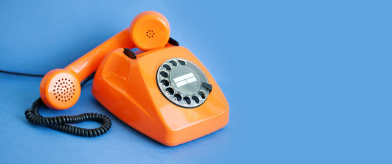 Busy retro phone orange color, handset receiver on blue background. copy space