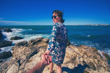 follow me girl. young woman in blue dress and sun glasses with the ocean on a background