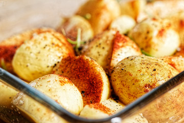 Potatoes in spices in the glass vessel prepared to be baked