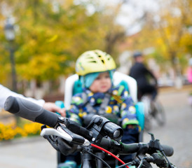 Electric bicycle lantern on the bicycle handlebar on a blurred background with a small child in a bicycle helmet