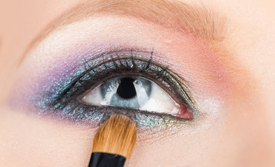 Fashion make up for women. Young woman eye, evening make up. Close up of blue woman eye with shiny evening makeup. Professional woman make-up for eyes. Cosmetics brush in front of female eye