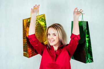 beautiful young girl in a red shirt on a white background holds shopping bags in her hands. Idea of shopping, sales