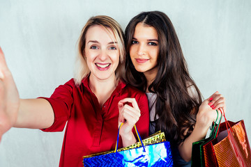 2 women, an Indian and a European hold packages for shopping in their hands and make selfies. The idea of sales, discounts, shopping