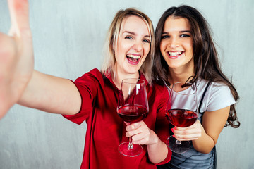 happy European and Indian woman holding a glass of red wine and making selfie. Friendship between peoples, alcoholism