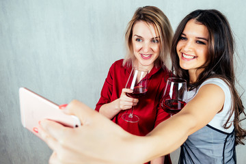 happy European and Indian woman holding a glass of red wine and making selfie on a smartphone. Friendship between peoples, alcoholism