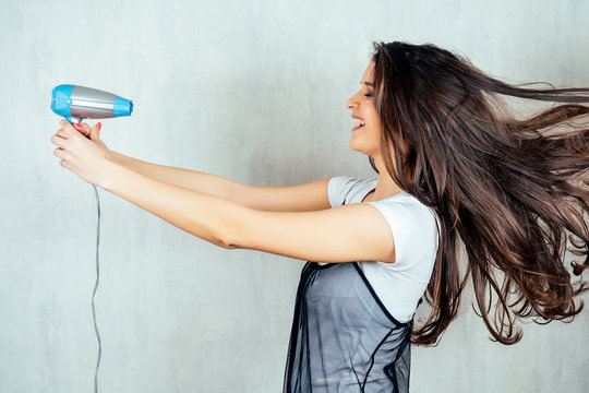 Indian woman holding blue hair dryer in hands on white background