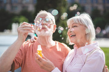 Mature man is blowing bubbles with joy outdoors. Senior lady is holding bottle of soap water and feeling excited and happy